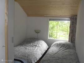 Kleinste slaapkamer met o.a. twee eenpersoonsbedden en een garderobekast.
