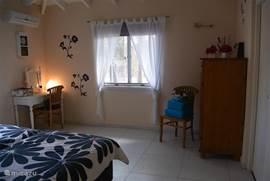 Masterbed room, sfeervolle slaapkamer, met 2x  1 persoon springbox bedden, 2 nachtkastjes, toilettafel, Airco en plafond ventilator, aangrenzend de ruime badkamer met de Walking Closet, uitzicht op de tuin.