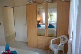 Slaapkamer nr.3 met 2 persoon springbox bed, grote hang\legkast, 2 nachtkastjes en Airco, Uitzicht op de tuin, het resort en het eiland, je kijkt hier n.l. over het resort en het eiland heen terwijl u in de slaapkamer alle privacy heeft.