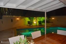 De villa in de avond met sfeervolle verlichting. Het licht in het zwembad veranderd van kleur.