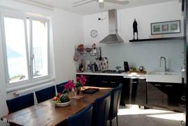 The kitchen with large dining table and dishwasher, fridge-freezer, oven, microwave, 4-burner stove, hood.