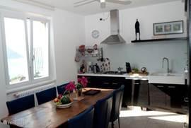De keuken met royale eettafel en vaatwasser, koel-vriescombinatie, oven, magnetron, 4-pits gasstel, afzuigkap.