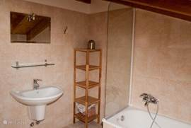 The bathroom in the attic, with bath, sink, toilet and bidet.