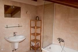 De badkamer op zolder, met ligbad, wastafel, toilet en bidet.