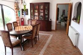 Eetkamer met vitrinekast gevuld met Nederlands-talige lectuur, alsook enkele gezelschapspelletjes. Rechts het doorgeefraam naar de keuken.