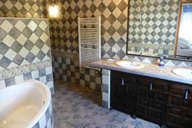 Grootste badkamer met hoekbad/douche, dubbele lavabo/toilet. Uitzicht op de tuin