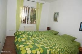 Slaapkamer die zicht heeft naar de patio, ook allen met rolluiken en muggenramen. Plafondventilator