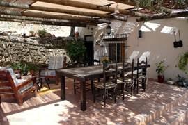 Patio met salon, grote tafel en stoelen, waar het dak kan open en toe geschoven worden. Een aanrader bij te warm en s avonds bij de apero.