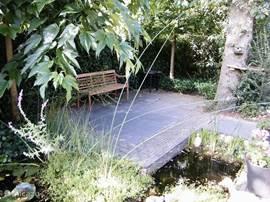 Het is goed toeven op het terras naast de ondiepe vijver.