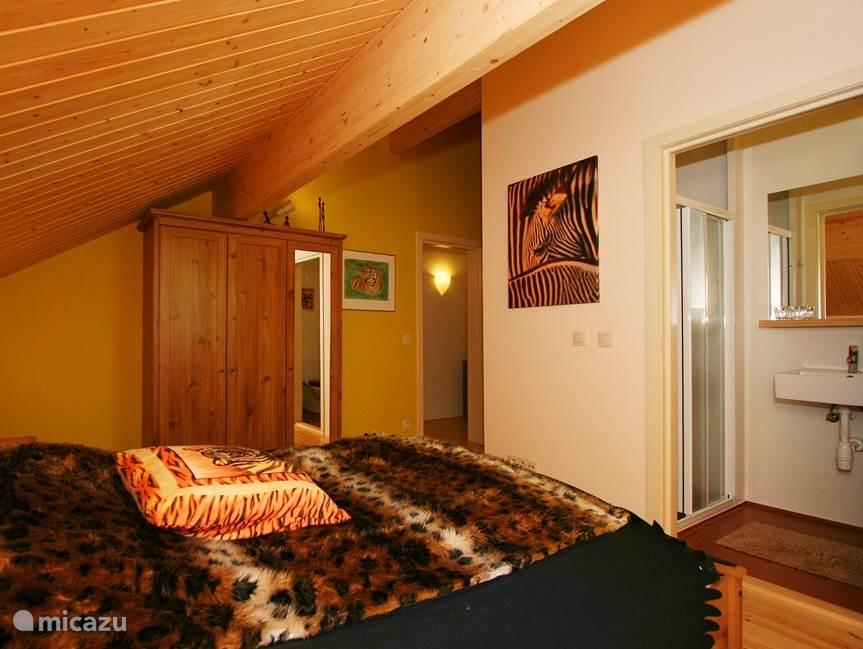 De safari slaapkamer is ingericht naar Afrikaanse stijl, kleuren en details vergroten de sfeer. Het interieur: tweepersoonsbed, tweepersoonsmatras, eenpersoons dekbedden en hoofdkussens, een kledingkast, nachtkastjes en stoelen. Aangrenzend is de eigen badkamer met de douche, wastafel en toilet.
