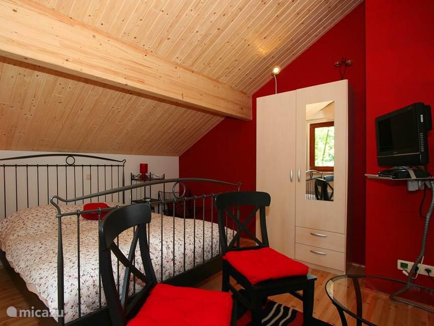 In de romantische slaapkamer overheerst de kleur van de liefde. Het interieur: tweepersoonsbed, tweepersoonsmatras, eenpersoons dekbedden en hoofdkussens, een kledingkast, nachtkastjes, een zitje en een TV. Aangrenzend is de eigen badkamer met de douche, wastafel en toilet.