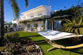 Tuin aan de voorzijde van het huis, voorzien van een hangmat waar men heerlijk onder de palmbomen kan genieten
