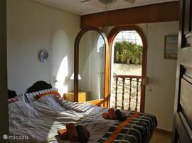 1e slaapkamer (master bedroom) - interieur - grote inbouwkast,  plafondventilator met openslaande deur richting balkon met fantastisch haven- en zeezicht.