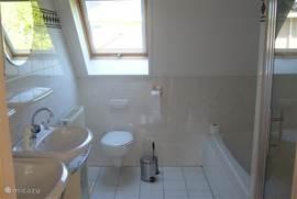 Ruime badkamer met bad en apparte douch
