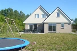ruime tuin met trampoline en speeltoestel
