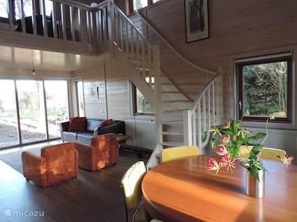 De trap leidt naar de vide, waar twee grote leesfauteuils en een boekenmolen staan.