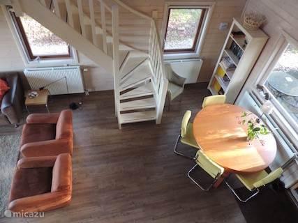 De woonkamer vanaf de vide: een gezellig leeshoekje en de eettafel met zicht op het terras voor.
