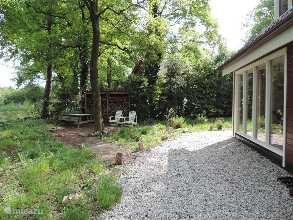De achterzijde van het huis met de houtopslag, waarin het goed toeven is voor vogels en insecten.