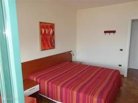Ruime slaapkamer met 2x 1-persoonsbed, 2 nachtkastjes met verlichting, poef/1-persoons- klapbed en kleedspiegel.