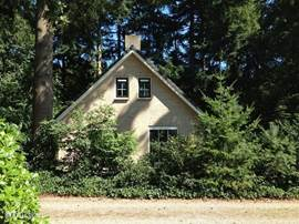 Een zomerse opname van de voorkant van het huis (140 m3). Zoals u ziet half in het bos gelegen, met zowel voldoende zon als schaduw in de tuin van ruim 700 m2.