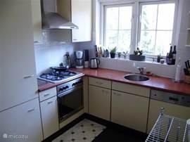 De keuken. U hoeft hier weinig tot niets te missen van wat u thuis ook gewend was. Soms komt er, als u staat te koken, spontaan een eekhoorntje langshuppelen voor het raam. Achter u trouwens nog een grote voorraadkast en links, uit het zicht, de deur naar de bijkeuken met wasmachine - en droger.