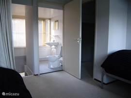 De beide eenpersoonsoonsbedden (latex matrassen) op de overloop en een kijkje in de tweede badkamer/toiletruimte boven. Achter mij een raam over de gehele breedte (dakkapel). Er zijn ook nog twee opklapbedden beschikbaar, waardoor er 8 slaapplaatsen totaal ontstaan.