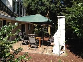 Zomers plaatje van het terras. Links de openslaande verandadeuren. BBQ rechts en een achtpersoons tuintafel met langwerpige parasol in het midden. Het is hier ongeveer drie uur in de middag, ergens augustus 2012.