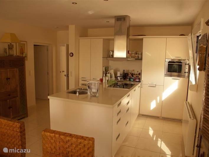 Ruime moderne keuken met een groot kookeiland voorzien van inductiekookplaat, oven/magnetron,  vaatwasser en veel kastruimte.