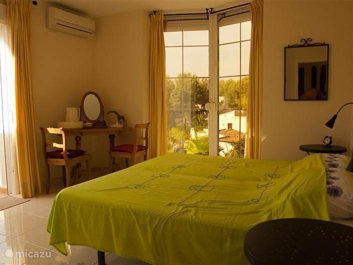 Slaapkamer met groot raam en uitzicht op de tuin.