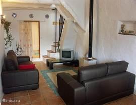 In dit deel van de (lange) woonkamer bevindt zich de zithoek met tv, dvd, boekenkast en muziekinstallatie. Achterin de deur naar de badkamer en de trap naar de 2e verdieping.