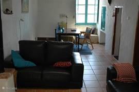 Vanaf de woonkeuken komt U via een open trap(links) in de woonkamer. Op deze foto ziet U het deel van de woonkamer met het bureau, raam, internetaansluiting, en een inbouwkastje, waar o.a. wandelkaarten en tips voor de omgeving in liggen. Rechts de deuren naar de 1e en 2e slaapkamer.