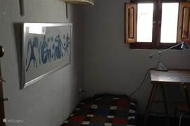 2e (werk)slaapkamer met opklapbaar bed (met matig matras), tafel, grote dichte kledingkast en open legplanken met strijkijzer, stofzuiger etc.