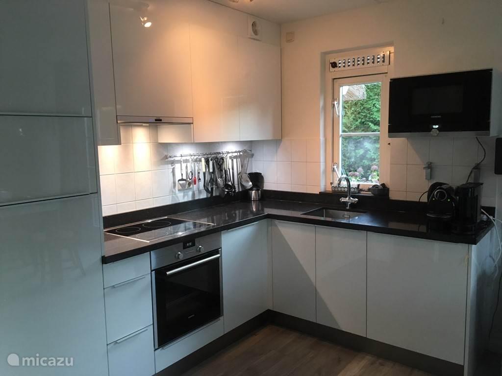Moderne, open keuken met alle benodigde apparatuur met o.a. een vaatwasser.
