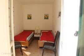 Slaapkamer met twee aparte bedden. die ook tegen elkaar gezet kunnen worden. Deze kamer heeft twee openslaande deuren.