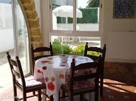 Vanuit de patio een blik op de zijkant van het huis. De patio heeft een schuifraam en openslaande deuren naar het zijterras en de tuin.In de tuin zijn citroenbomen, oleanders, palmen, een perzikboompje en valse sinasappelen waar je met heel veel suiker erbij marmelade van kan maken.