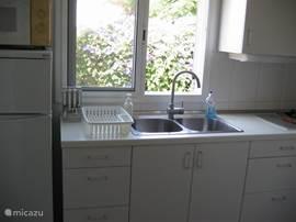 De keuken is van alle gemakken voorzien. Er is een aparte ruimte waar de boiler hangt en er onder bevindt zich de wasmachine. Een magnetron met grill staat boven op de ijskast. Er wordt gekookt met butagas op een vier-pits gasfornuis.