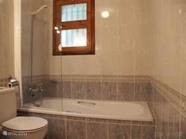 De mooie grote badkamer ligt naast de ouderslaapkamer en is voorzien van een ligbad met douche, twee wastafels, wandkastjes en een toilet.