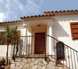 De voordeur is aan de zijkant van de woning gesitueerd. Deze bereikt men via een royale stenen trap.