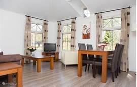 Lichte woonkamer door de vele ramen. Gezellig ingericht. In de woonkamer staat een 2- persoons bank en 2 comfortabele fauteuils.