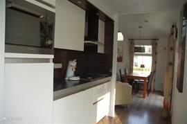 Moderne open keuken voorzien van vaatwasser, combi-magnetron, koelkast en gaskookplaat.