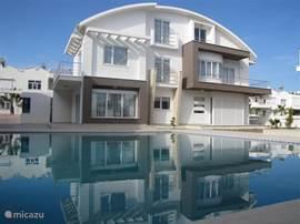 De 2 onder 1 kap villa ligt direct aan het heerlijke zwembad