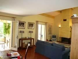Wohnzimmer mit 2 Flügeltüren zur Hauptterrasse. Die Bestuhlung ist rund um den Kamin angeordnet und daneben die TV mit Sat-Decoder und DVD-Player. Überall im Haus und die Umgebung ist Wifi zur Verfügung.