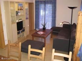 De woonkamer is voorzien van een grote hoekbank en een extra fauteuil. In het wandmeubel staan de tv en de radio/cd-speler.