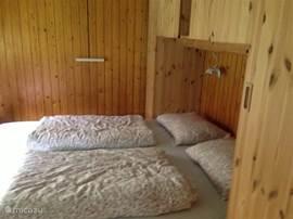 Beneden een ruime slaapkamer met boxspringbedden en kastenombouw.