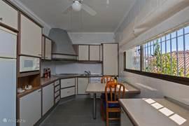 Keuken, leuk uitzicht op tuin en van alle gemakken voorzien. In de keuken kan je ook zitten en even lekker Spaans eten, net als in de woonkamer of liever nog op de terrassen lekker in de schaduw met een zeewindje.