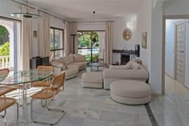 Gezellige moderne woonkamer met haard, en je loopt zo naar de terrassen die overdekt zijn en door naar de prachtige tuin.