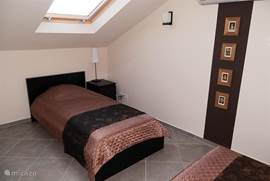 Derde (zolder) slaapkamer met twee eenpersoonsbedden, uiteraard voorzien van airo en een te verduisteren zolderraam. Ook deze kamer heeft een eigen badkamer en een grote inbouw kledingkast met twee grote lades en een passpiegel