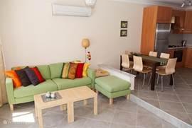 Woonkamer met keuken,modern en gezellig ingericht, voorzien van airconditioning, 3 zits bank, 2 poefen, tafel, TV en DVD speler. Vanuit de woonkamer loopt u direct het terras op en kunt u een frisse duik in het 25 meter lange zwembad nemen