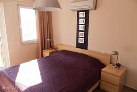 Slaapkamer met king size twee persoonsbed. Voorzien van airco. Alle slaapkamers hebben een eigen badkamer. Via de openslaande deur komt u op het balkon met een schitterend uitzicht over zwembad, tuin en granaatappel boomgaard, passpiegel aanwezig