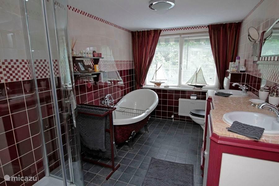 In de badkamer in Engelse stijl vindt u een bad op pootjes, een badmeubel met twee wastafels, een tweede toilet en een ruime douchecabine met regendouche.
